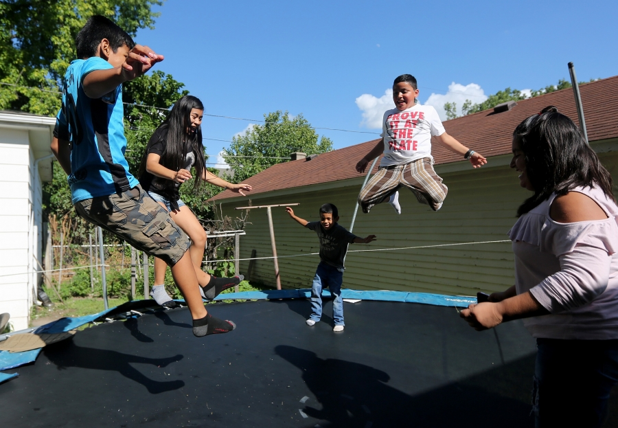 Children jump on trampoline outdoors