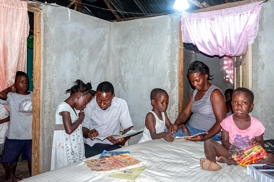 "Frantzy Monfilston, a teacher who lives with his family of four in Chansolme, helps his children finish their homework. Before Monfilston became a beneficiary of ""Ma Maison Eclairée"" in May 2017, he says, his home had no electricity."