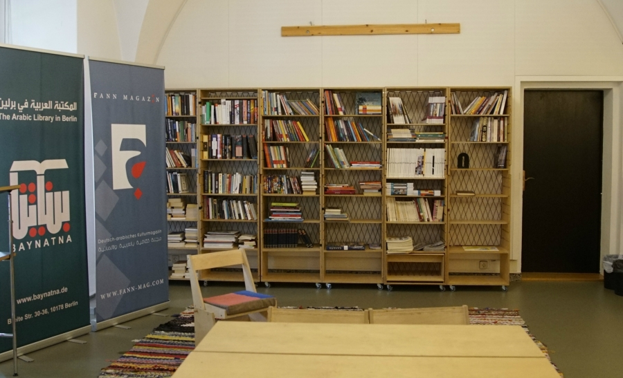 The library is built out of custom bookshelves and tables that are designed to be moved and stored easily, in case of a change in location. It's decorated with rugs woven from old clothing.