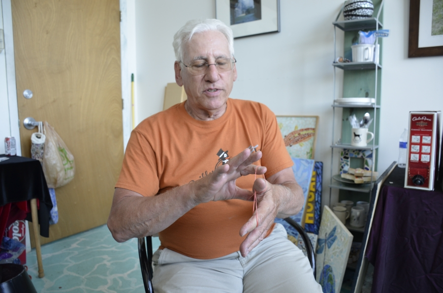 Bruce Ward performs a magic trick with rubber bands. The former steel worker has reinvented himself with a number of jobs — including as a photographer, videographer, and magician — since being laid off from the mill in Bethlehem two decades ago.