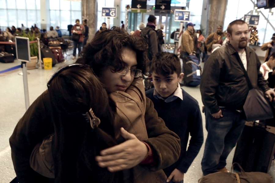 Woman hugs young man with family standing behind them