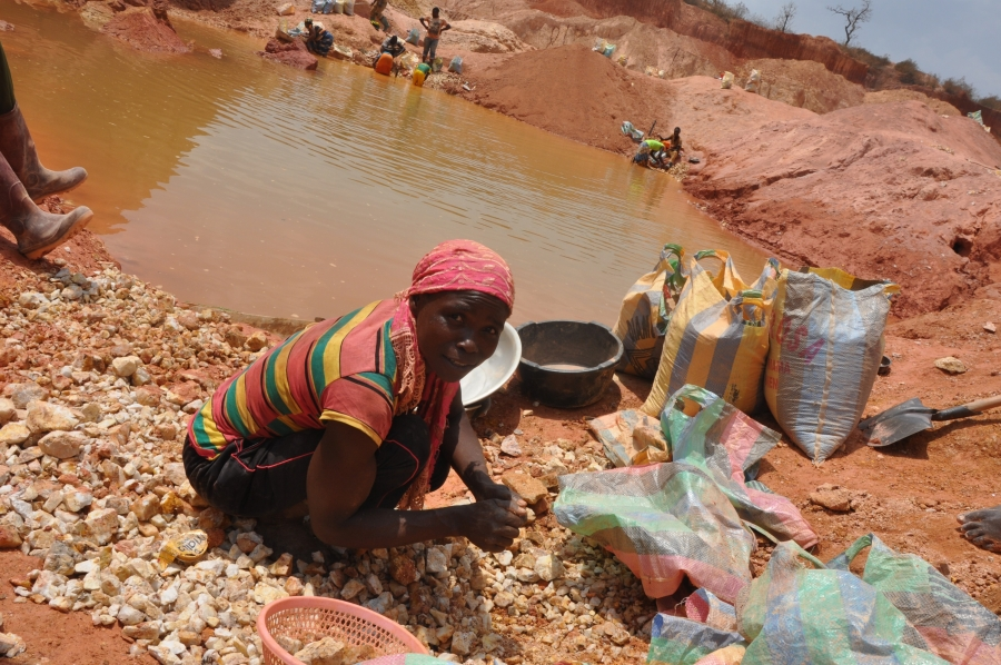 Sidonie Maboue, 45, a widow and mother, picks up small rocks from a mine site abandoned by Chinese miners. These pebbles are later crushed and sieved to collect gold.