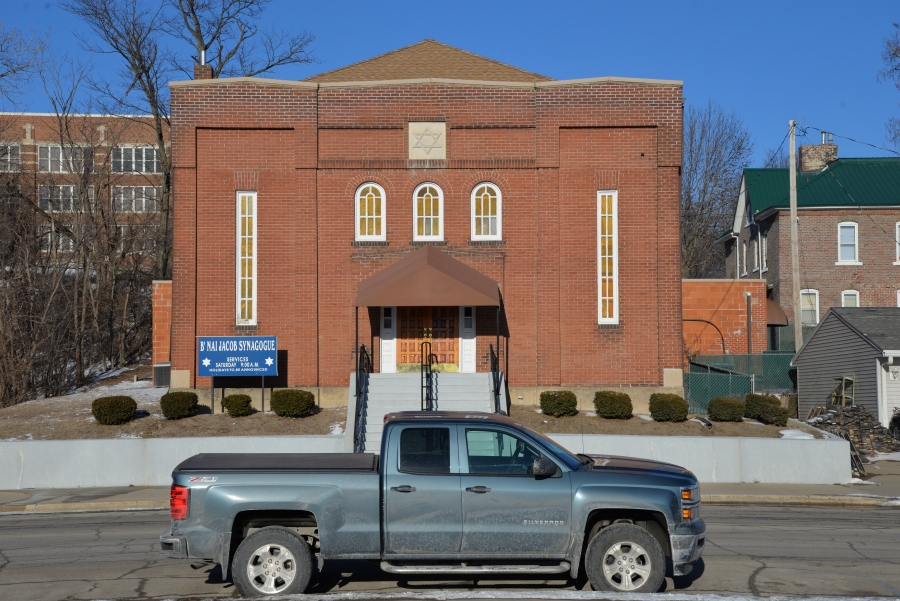 Small brick building with synagogue sign in front, on small street. Truck in foreground.