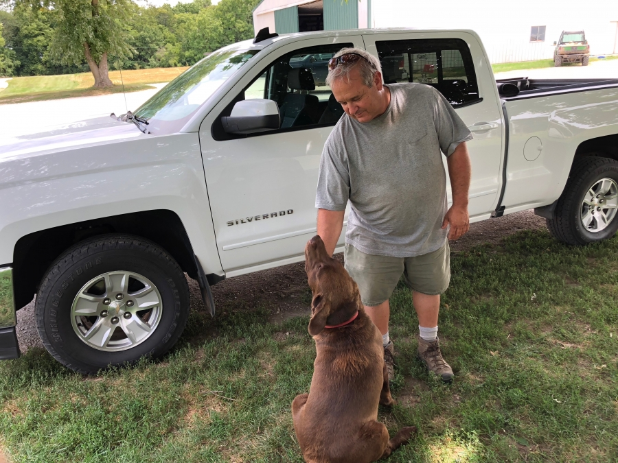 Farmer Dale Hadden and his dog Boomer. Hadden worries that if commodity prices stay depressed into next year, there will be an exodus of people farming in Illinois