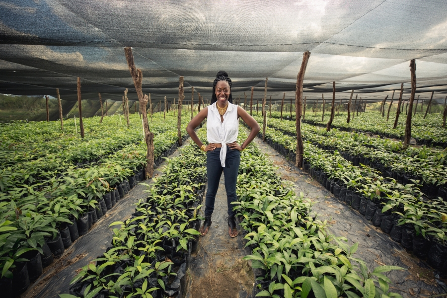 Woman stands in middle of rows of plants, greenhouse, smiling with hands on hips
