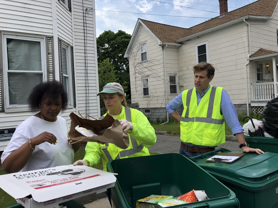 Julia Greene (center), the recycling coordinator for the city of Lynn, Mass., gives resident Diane Thomas (left) a brief tutorial on recycling. Cody Marshall, with the Recycling Partnership, looks on, offering words of encouragement.