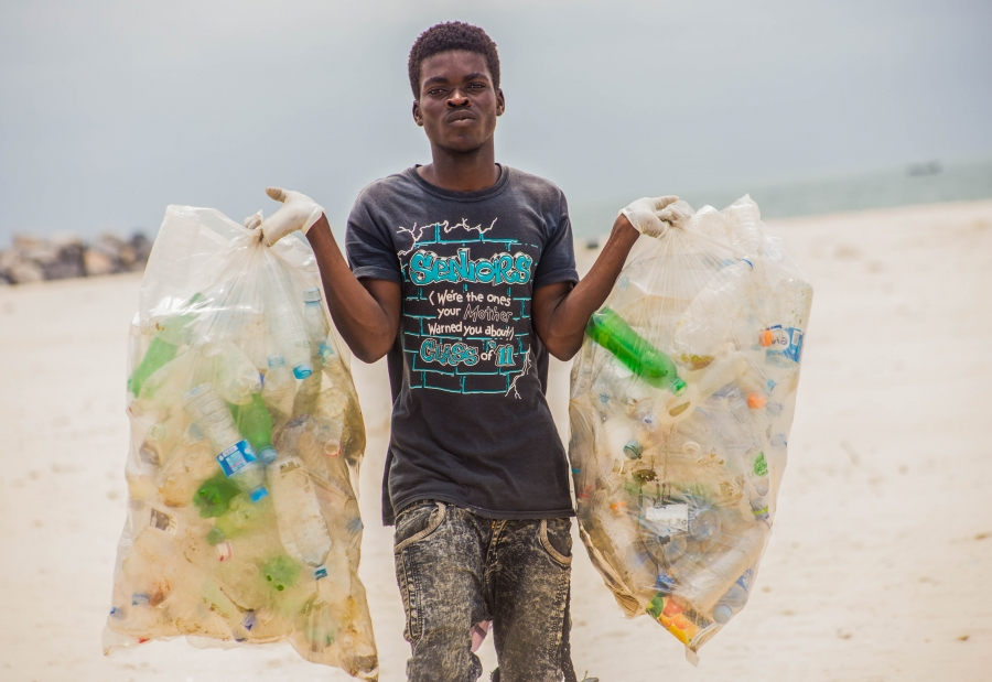 A volunteer in Nigeria collects waste on a beach during the Ocean Conservancy's annual International Coastal Cleanup. Plastic straws were the seventh most common type of trash found last year.