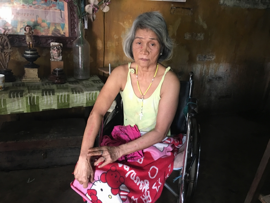 an older woman with a pink skirt sitting in a wheelchair