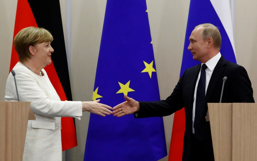 Russian President Vladimir Putin and German Chancellor Angela Merkel shake hands following a joint news conference in the Black Sea resort of Sochi, Russia, May 18, 2018.