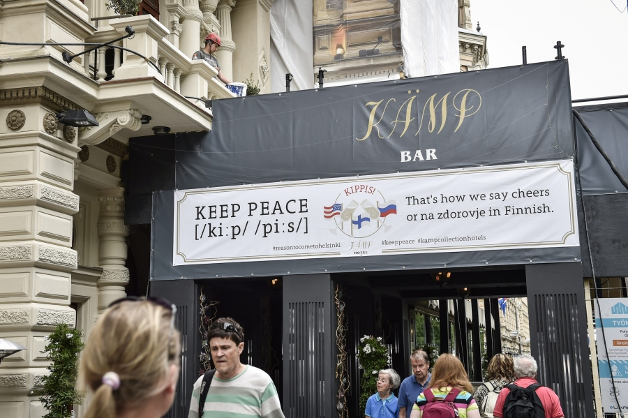 "A sign at a bar reads: ""Keep peace. That's how we say cheers ... in Finnish."" The sign also shows a Russian flag and a US flag."