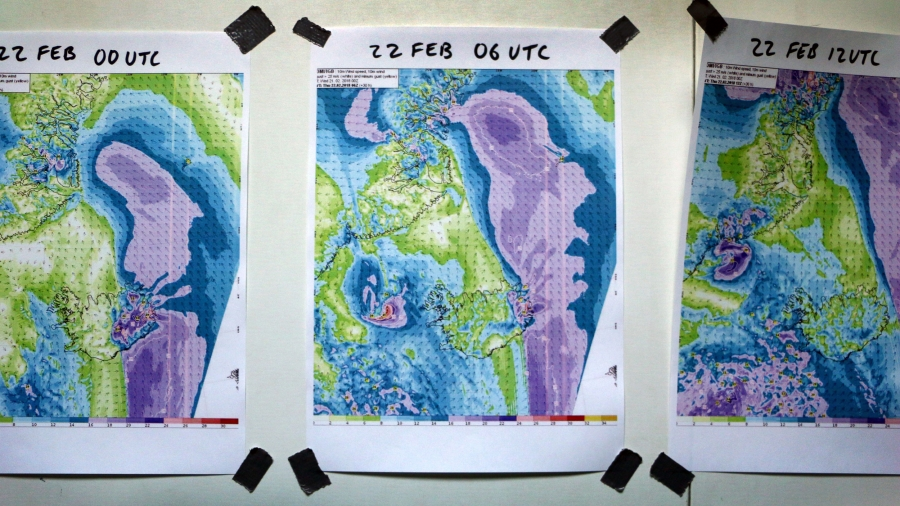 Color maps depicting wind velocities are taped to a wall and dated