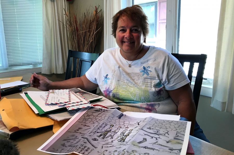 A woman sits at a table with a drawing and some letters piled in front of her.