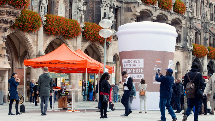 A giant inflatable coffee cup is set up in a public square. Behind it is an old Gothic church.