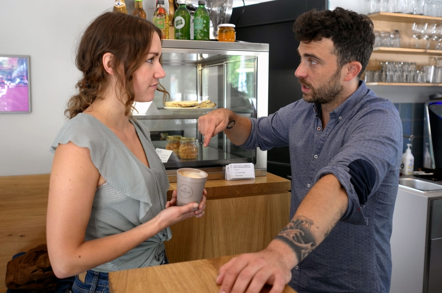 A woman and a man stand in a coffee shop. She is holding a reusable Recup.