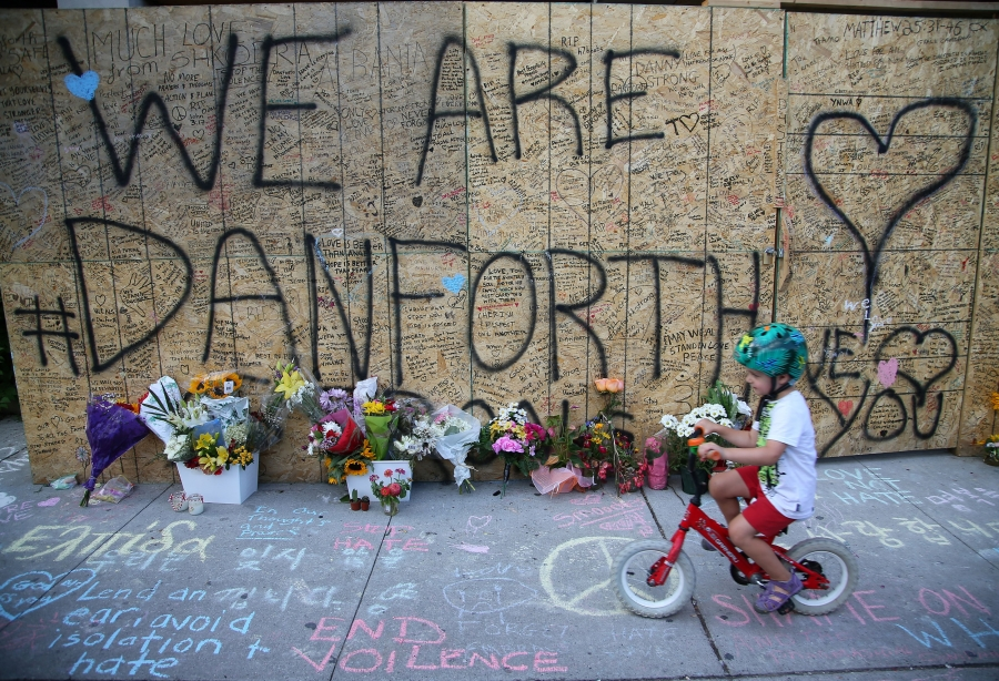 "A small boy rides a bicycle past a plywood wall that says ""We are Danforth"" inscribed with messages, hearts and flowers."