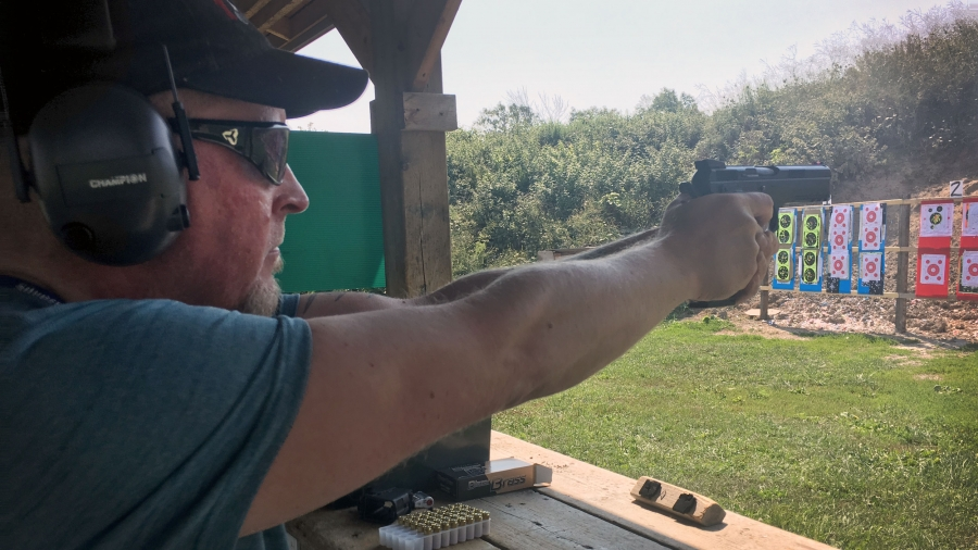 A man points a handgun at a target on a shooting range