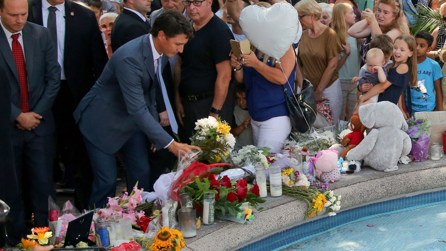 Canada's Prime Minister Justin Trudeau lays flowers at the site of a mass shooting. Around him is a large crowd assembled for a vigil.