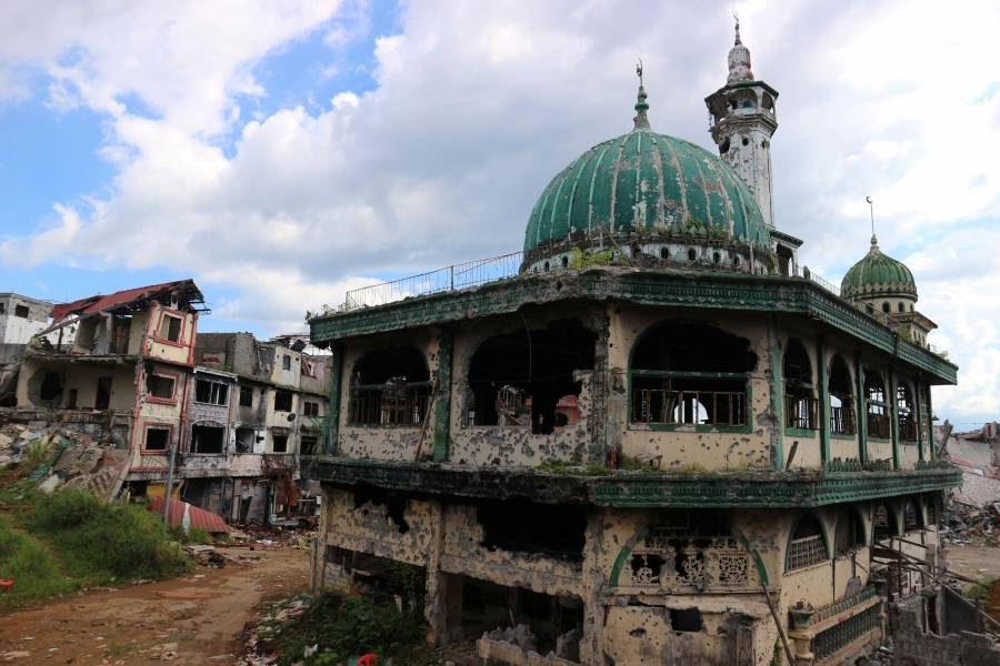 The dome of a damaged mosque rises among rubble in a city
