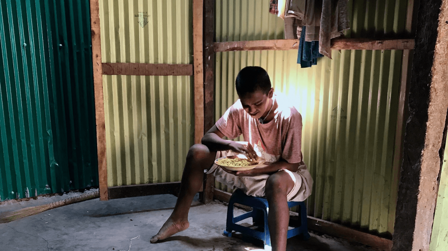 a young Rohingya man with intellectural disabilities sits in his makeshift home