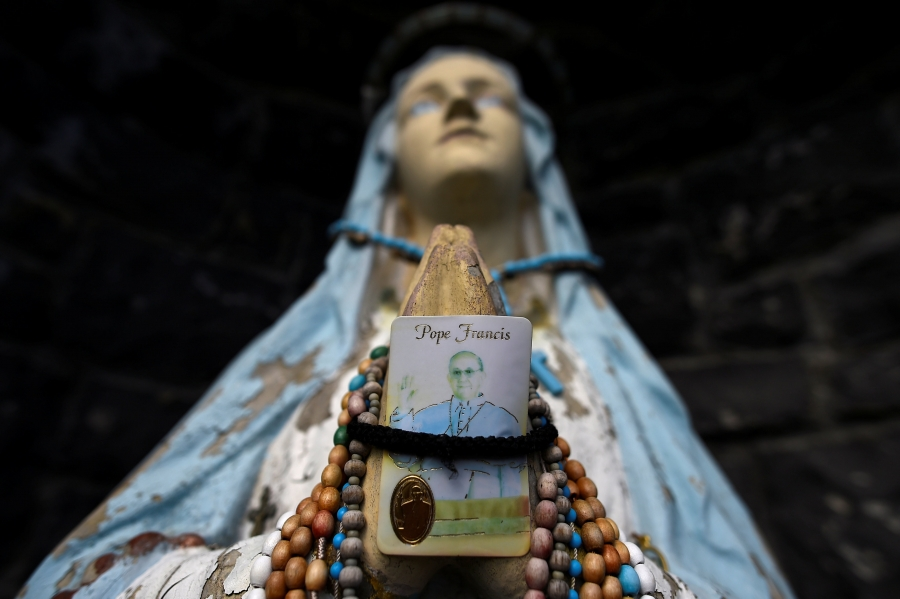 A religious grotto featuring a statue of the Virgin Mary holding aPopeFrancis prayer card