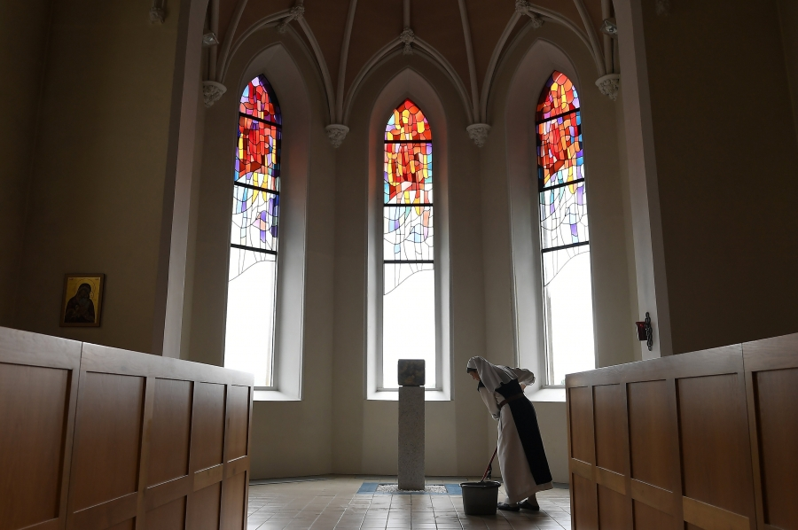a nun in white, wiping the floors in front of a stained glass window