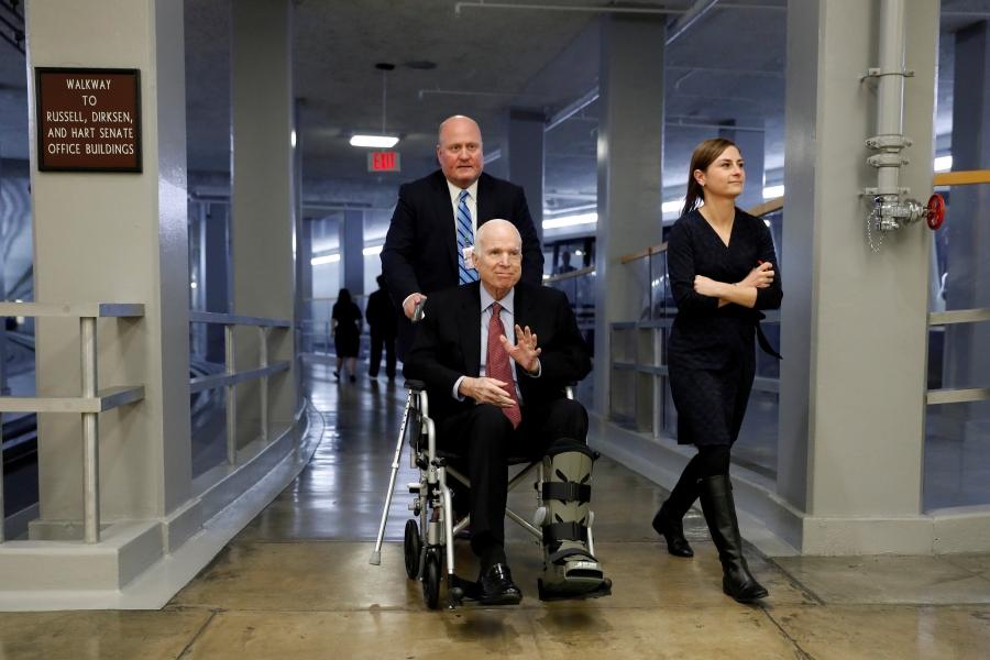 Senator John McCain sitting in a wheelchair, smiling and waving