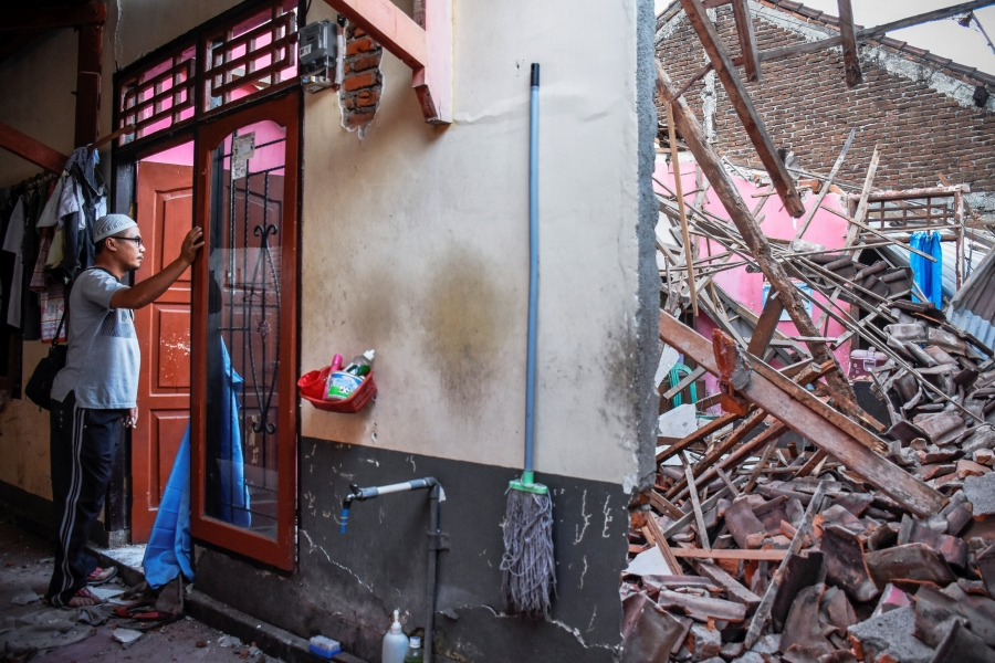 A man looks though a red doorway at debris from his partially collapsed home in Indonesia.