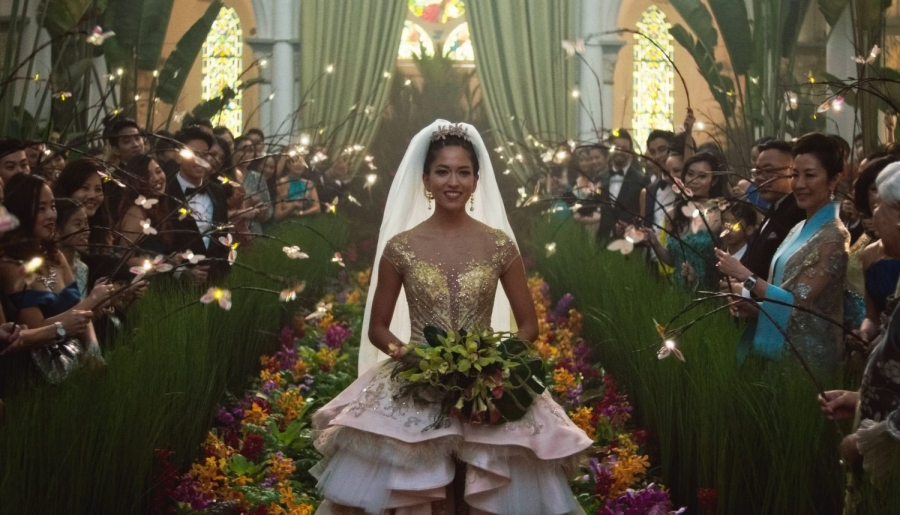 Woman in elaborate wedding dress waking down aisle, greenery, people looking on