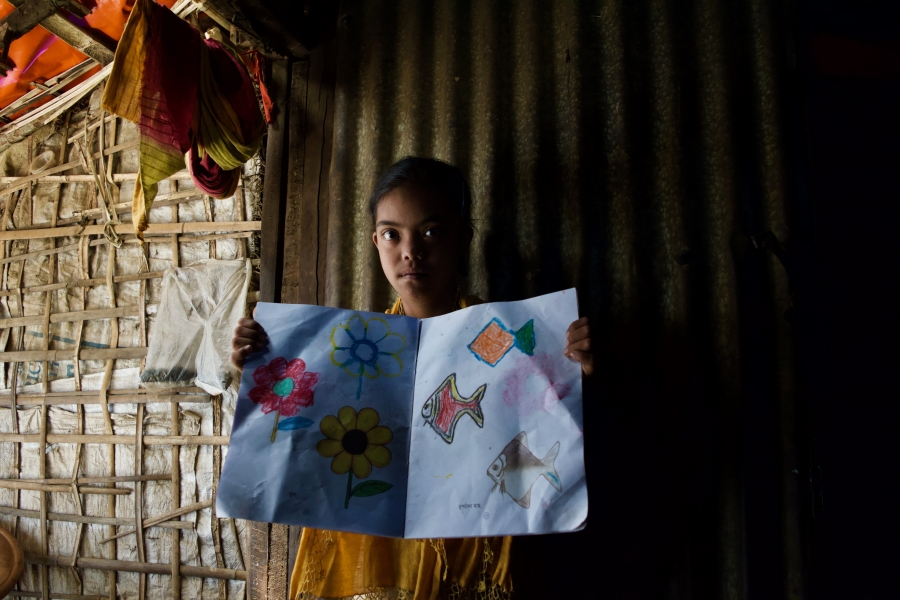 a young rohingya girl shows off a drawing