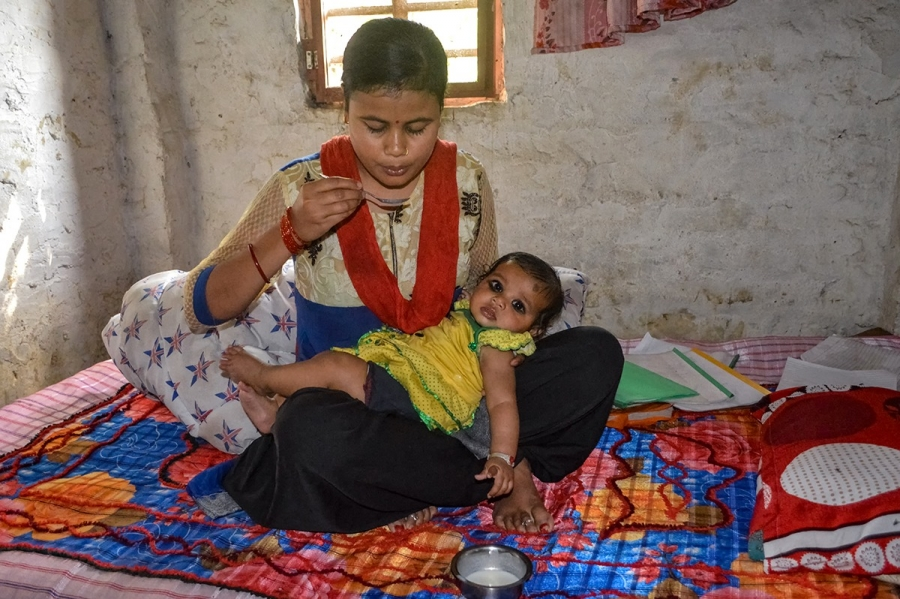a nepali woman feeds her small daughter