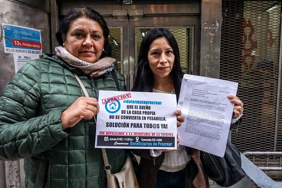 two women in argentina stand in front of a house for sale