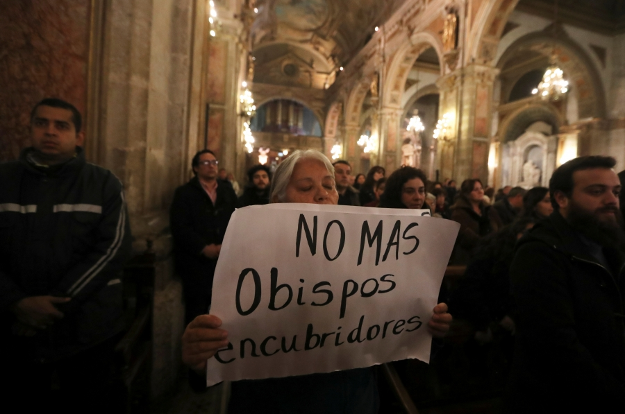 "A woman holds a banner that reads, ""No more bishops covering up"""