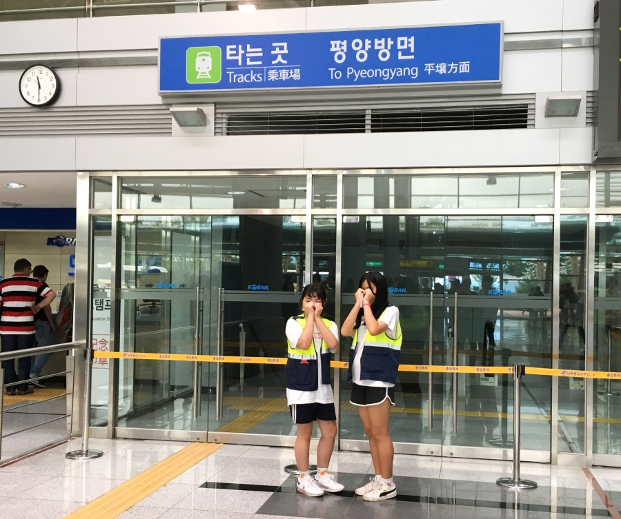 To women pose for photos at the Dorasan station