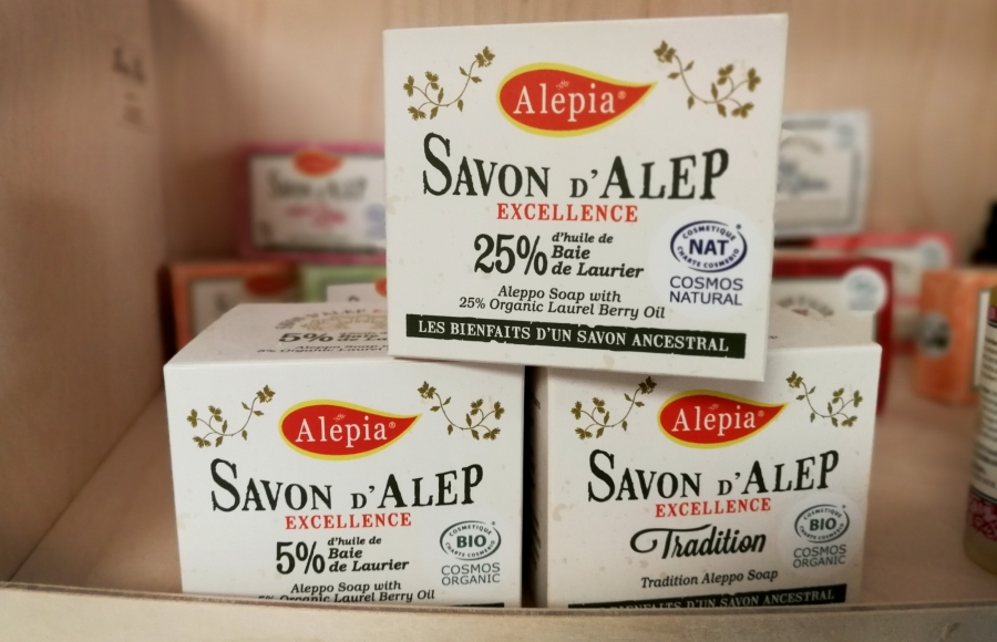 "Packaged soap sits on a shelf. The packages are written in French with the name ""Alepia."""