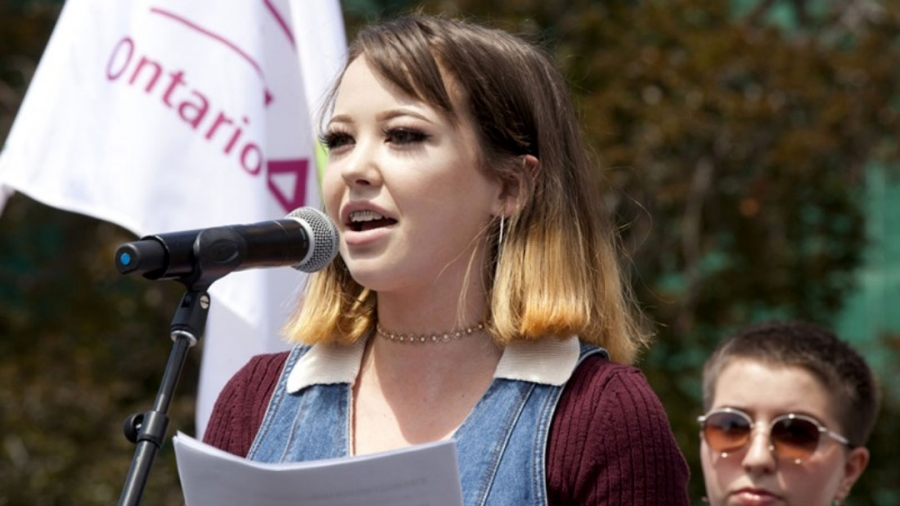 A young woman speaks at a microphone