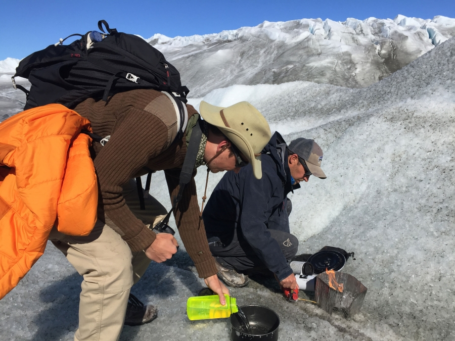 One man pours water into a pot and another starts a fire atop dirty snow