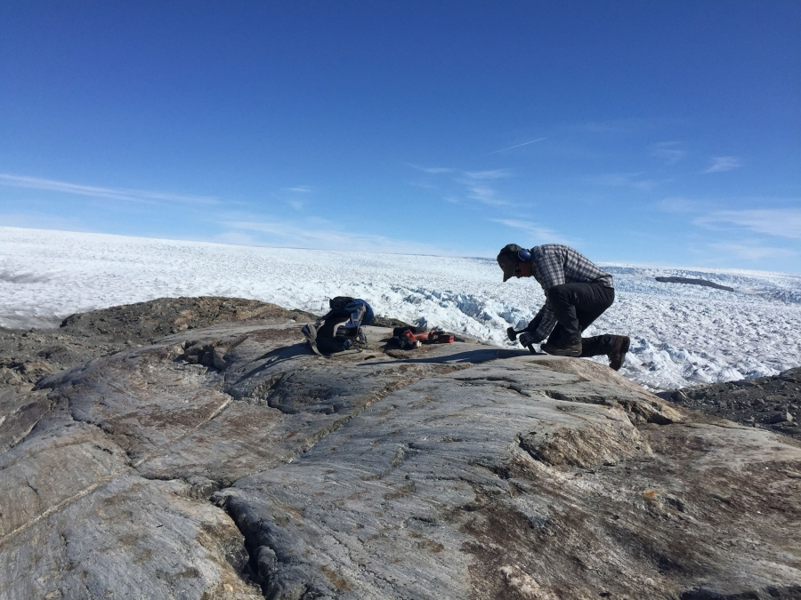 A man kneels on rock at the edge of the Greenland ice sheet.