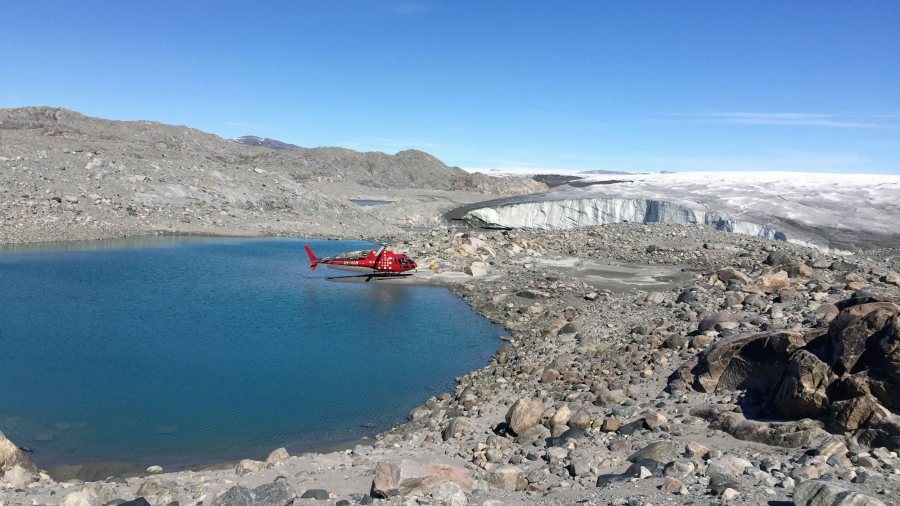 A red helicopter is landed on the edge of a blue lake on a rocky shoreline. Hills in the distance are covered in white ice.