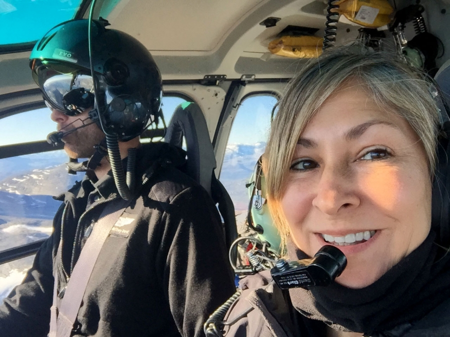 A woman wearing a headset smiles from inside a helicopter.
