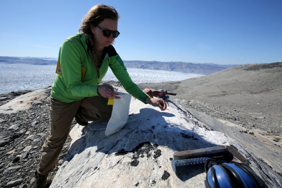 A woman picks something off a rock as a ice field glitters in the background