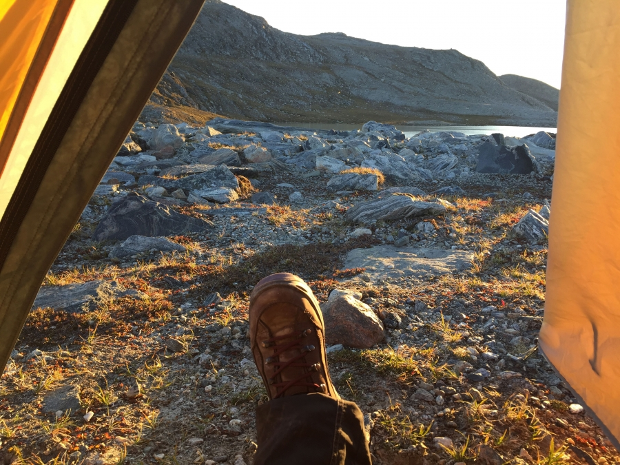 A woman's booted foot is framed by the walls of her tent as the golden sunlight spills over rocky terrain.