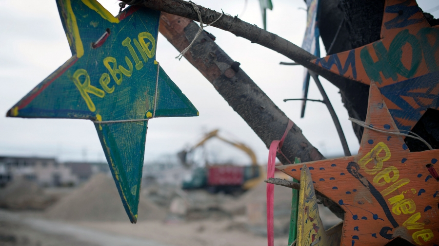 A wooden memorial star is seen hanging from a tree as heavy machinery excavate land in Breezy Point in Queens, New York, six months after the landfall of Superstorm Sandy in April 2013.