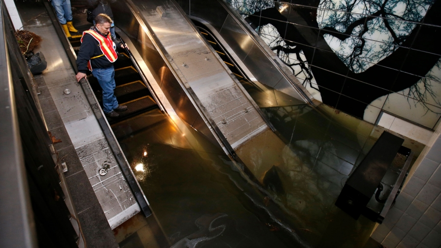 A man stands on an escalator looking down into a flooded subway station