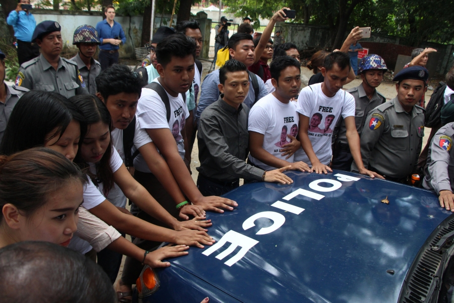Myanmar journalists stand in front of a police vehicle