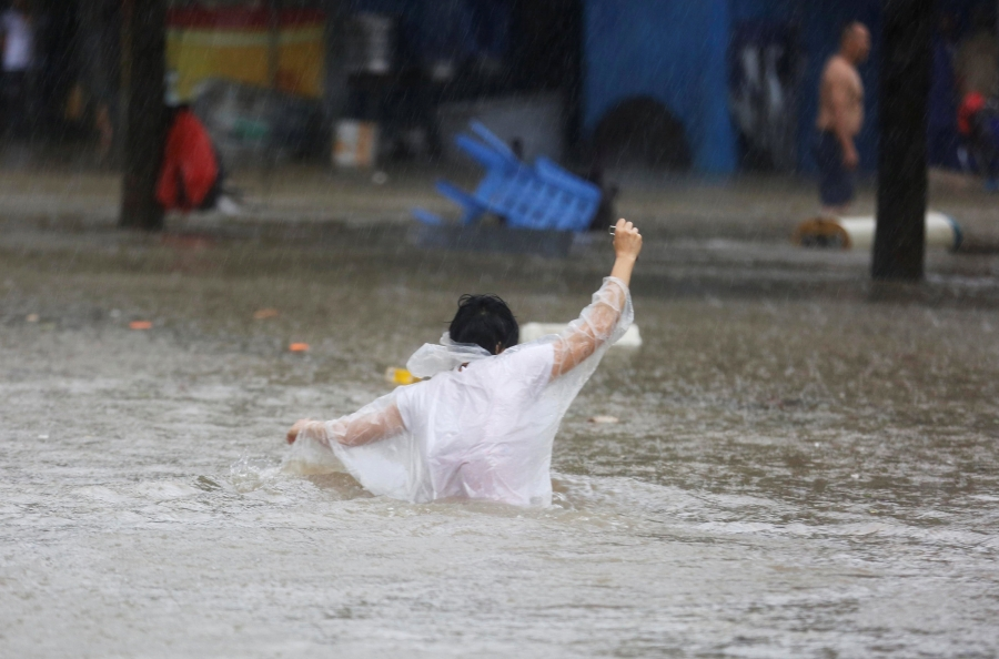 A pedestrian wades through waist-high floodwaters in a white poncho