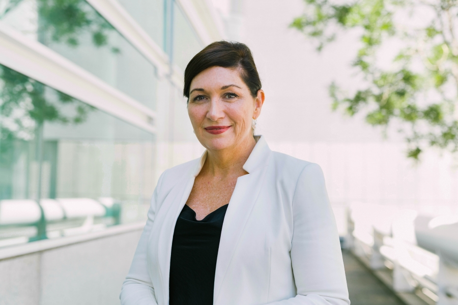 Leeanne Enoch is shown in a portrait photograph wearing a white jacket.