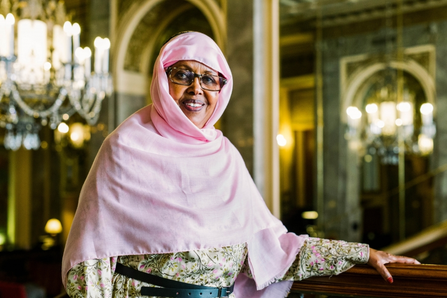 Shukri Haji Ismail is shown in a pink shawl with dark-rimmed glasses.