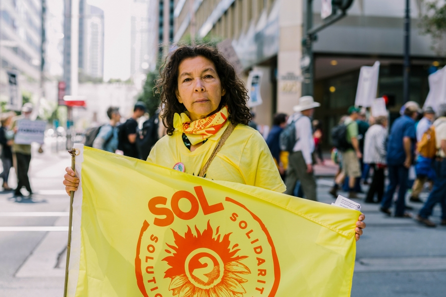 Alicia Rivera is shown holding a yellow flag during a demonstration in San Francisco, California.