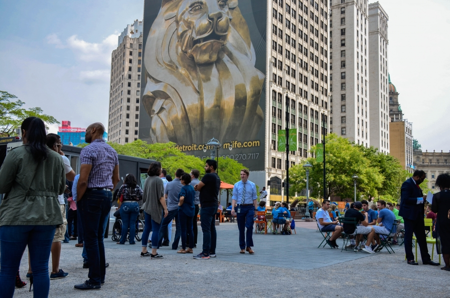 People are shown sitting at outdoor tables and standing in line for a food truck in downtown Detroit.