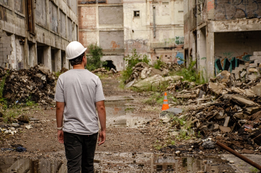 Jacob Jones is shown from behind in a hard hat walking through the debris and rubble of the former Packard Plant.